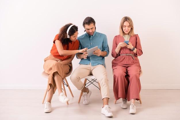 Uomo dai capelli castani che condivide informazioni su internet con una donna afroamericana in cuffie senza fili mentre la ragazza bionda manda un sms