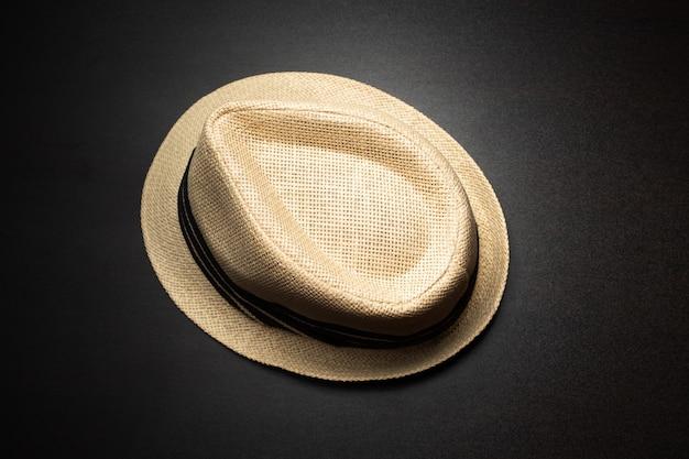Un cappello marrone è posto su un tavolo nero.