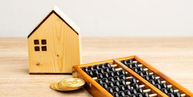 La casa marrone e la moneta d'oro con l'abaco cinese sulla vista frontale del tavolo marrone e sullo spazio della copia