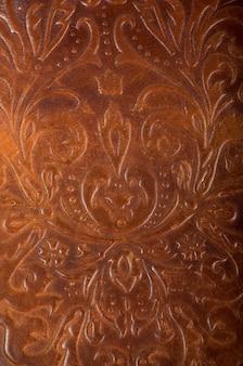 Libro in pelle marrone o copertina di giornale con un ornamento floreale decorativo.