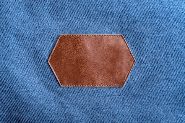 Etichetta in pelle marrone con cuciture su tessuto denim.