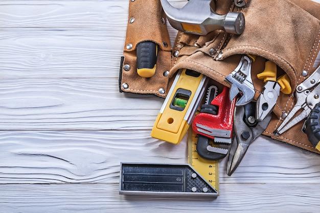 Cintura porta attrezzi in pelle marrone con attrezzi da costruzione su tavola di legno