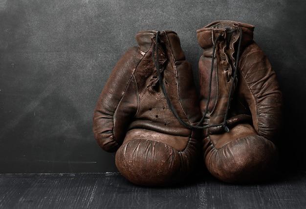 Guantoni da boxe vintage in pelle marrone su una superficie nera, attrezzature sportive