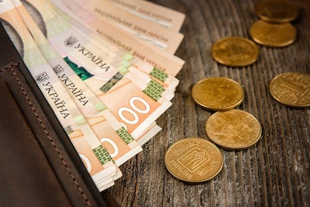 Portafoglio in pelle marrone con banconote e monete sulla vecchia superficie di legno