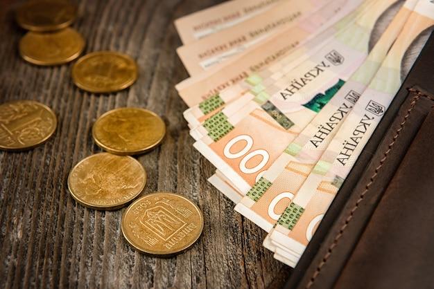 Portafoglio in pelle marrone con banconote e monete su una vecchia superficie di legno