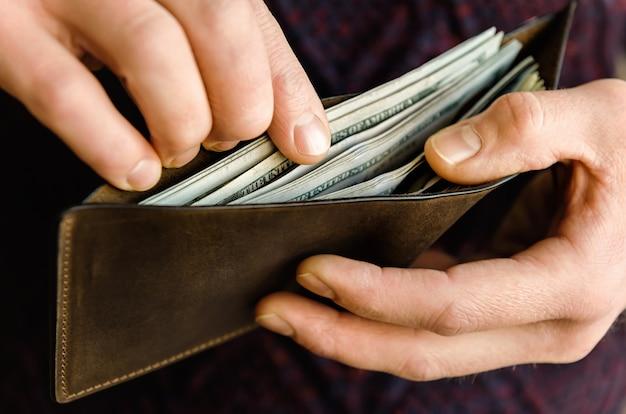 Portafoglio in pelle marrone con dollari in mano