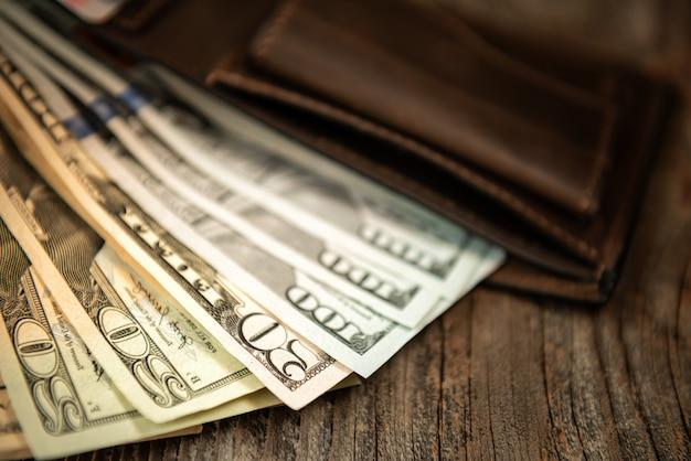 Portafoglio in pelle marrone con dollari su una vecchia superficie di legno