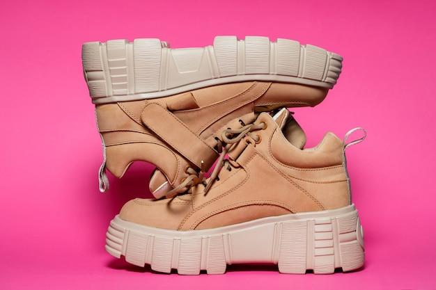 Scarpe da donna in pelle marrone con suole alte su sfondo rosa. calzature alla moda