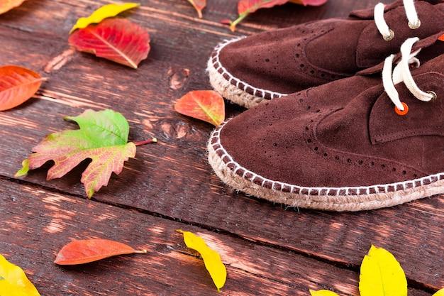Marrone uomo camoscio stivali espadrillas su fondo in legno con foglie. scarpe autunnali o invernali.