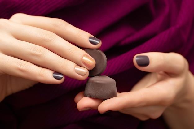 Design delle unghie marrone. mani femminili che tengono le caramelle di cioccolato.
