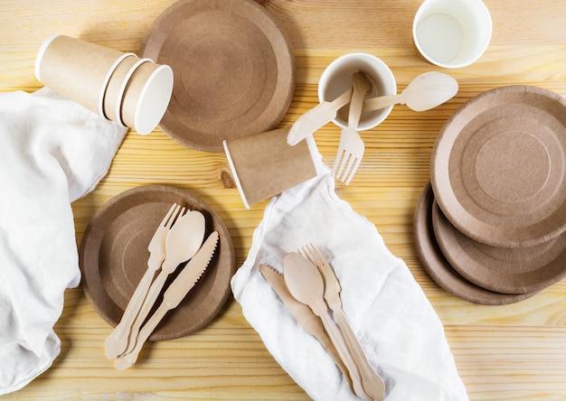 Bicchieri di carta marrone, piatti, posate in legno, tovaglioli di lino su fondo di legno