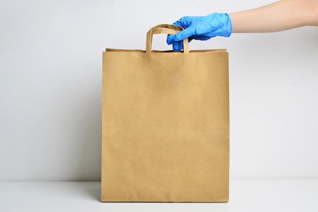 Un pacchetto ecologico di carta marrone tiene la mano di un fattorino in un guanto sterile isolato su un bianco