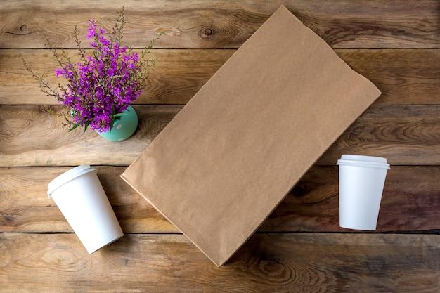 Shopping bag in carta marrone e due bicchieri di carta da caffè con mockup di coperchi con fiori di campo viola