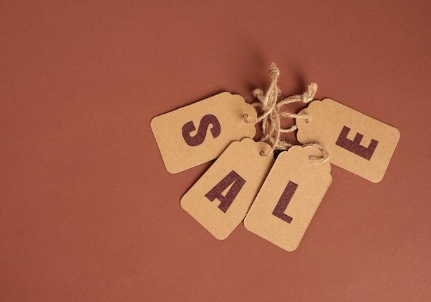 Etichette di carta marrone con vendita di iscrizione su marrone