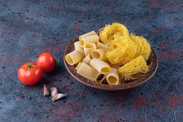 Un piatto marrone di tagliatelle nido con pomodori rossi freschi e aglio su una superficie scura.