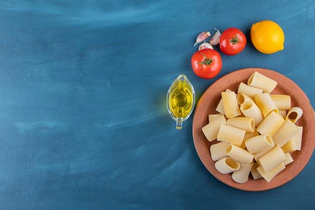 Un piatto marrone di pasta cannelloni crudi con pomodori rossi freschi e limone su sfondo blu scuro.