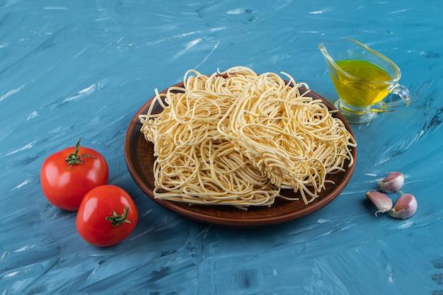 Un piatto marrone di pasta cruda con due pomodori rossi freschi e olio su una superficie blu.