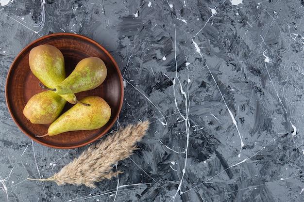 Piatto marrone con pere mature fresche su sfondo marmo.