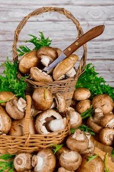Funghi portobello marroni in cesto di legno di vimini con decorazione di erba su fondo di legno.