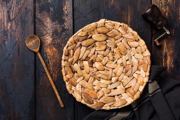 Piatto in rattan marrone e cucchiaio di legno sulla vecchia superficie di legno