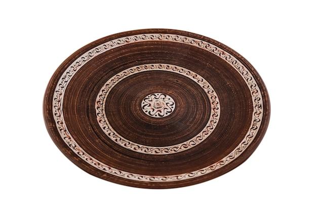 Vista dall'alto del piatto di argilla piatta rosso marrone isolato su bianco