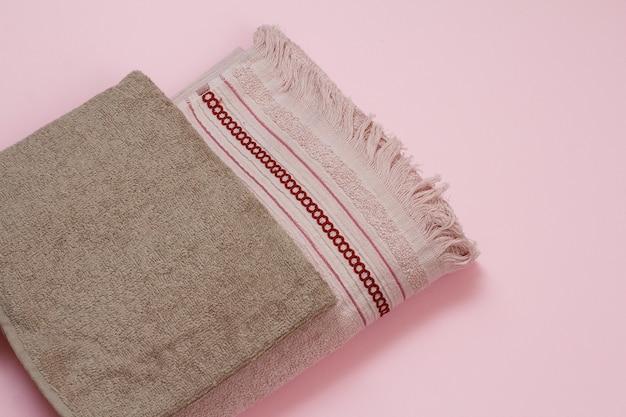 Asciugamani in morbida spugna marrone e rosso su sfondo rosa. vista dall'alto.
