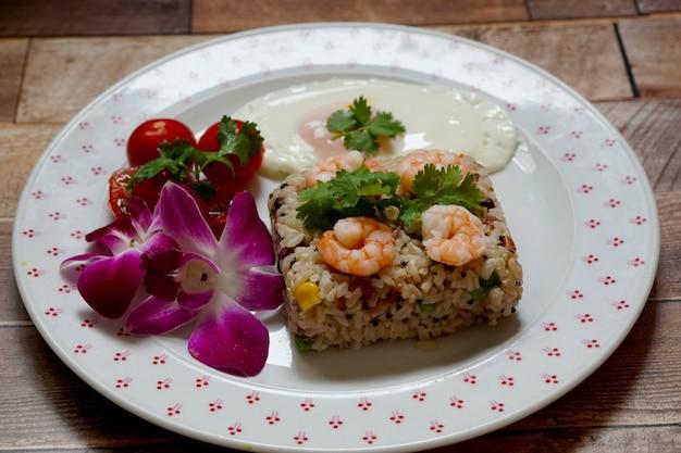 Riso integrale con gamberi e uovo fritto decorato con fiori di orchidea su un piatto