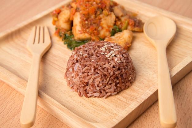 Riso integrale con pasta piccante saltato in padella con pesce in un piatto di legno