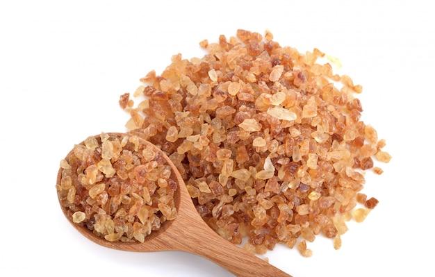 Zuccheri di roccia marroni in cucchiaio di legno isolato