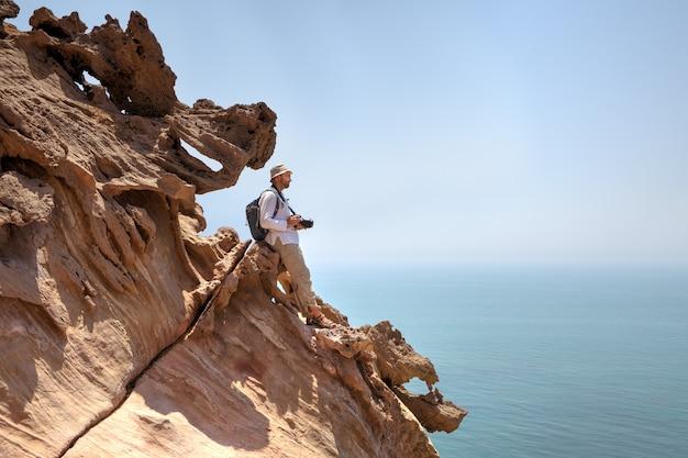 Rocce marroni contro il mare blu e la figura solitaria del fotografo viaggiatore sul bordo della scogliera, hormuz, iran.