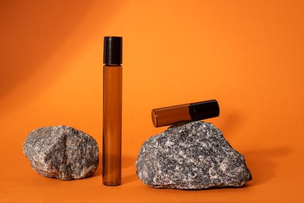 Siero marrone o bottiglia di vetro olio su arancia con pietra