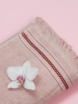 Asciugamano in morbida spugna marrone con gemma di orchidea bianca su sfondo rosa. vista dall'alto.