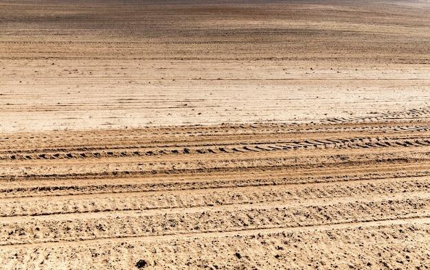 Terreno marrone di un campo arato durante la preparazione del terreno per la semina di un nuovo raccolto di piante