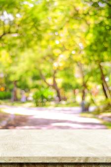 Tavolo in cemento marrone pietra per esposizione di prodotti alimentari e sfocatura sopra il giardino di alberi gialli sfocati in autunno, sfocatura parco naturale autunnale e piano in pietra concreta, mensola, bancone con luce bokeh