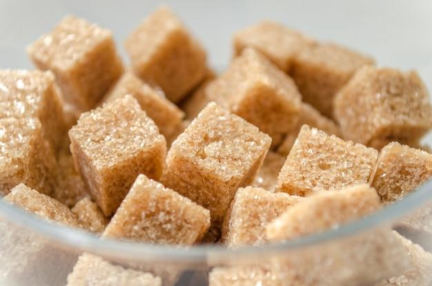 Cubetti di zucchero di canna in un bicchiere