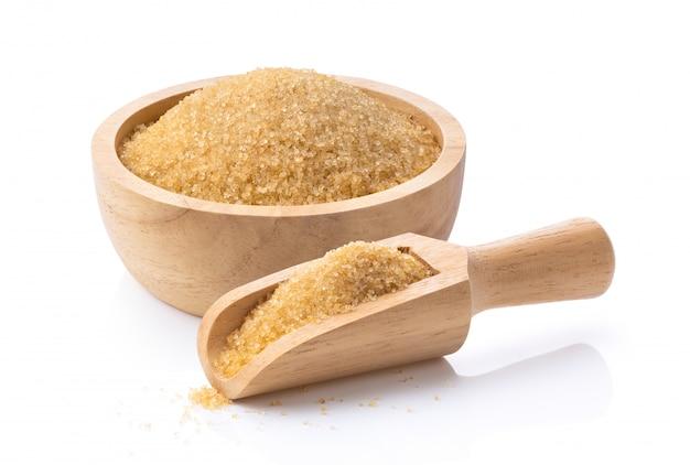 Zucchero bruno in mestolo e ciotola di legno su bianco