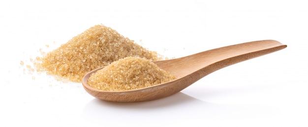 Zucchero bruno in cucchiaio di legno su bianco