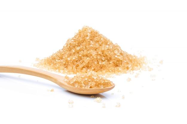 Zucchero bruno in mestolo di legno su fondo bianco