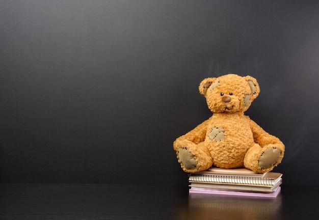 Brown orsacchiotto di peluche si siede su un tavolo di legno marrone, dietro una lavagna nera vuota, torna a scuola, copia dello spazio