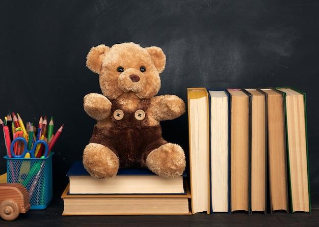 L'orsacchiotto marrone si siede su una tavola di legno marrone, dietro un bordo di gesso nero vuoto