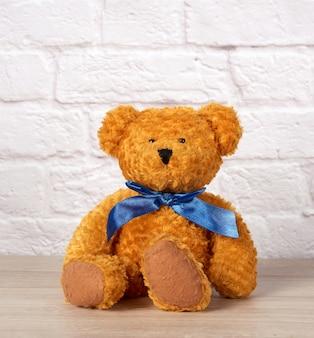 Orsacchiotto marrone si siede su bianco, giocattolo per bambini
