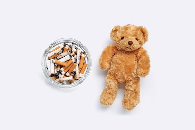 Orsacchiotto marrone con mozziconi di sigaretta e cenere su sfondo bianco.