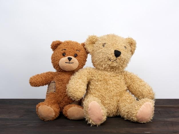 Gli orsacchiotti marroni stanno sedendo su una tavola di legno marrone, spazio bianco