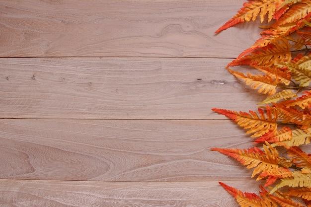 Trama di sfondo in legno vintage marrone e foglia rossa autunnale