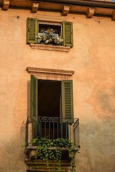Un muro marrone di una vecchia casa con balcone con persiane aperte e vasi di fiori.