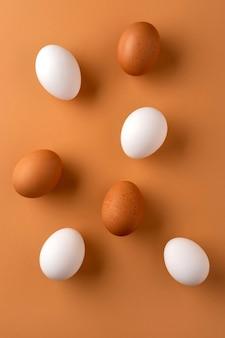 Uova di gallina marroni e bianche su fondo beige.