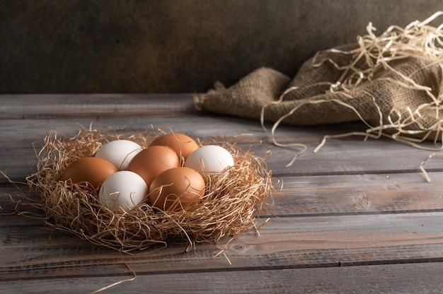 Marrone e bianco uova di gallina in un nido di paglia su fondo in legno. stile rustico. copia spazio