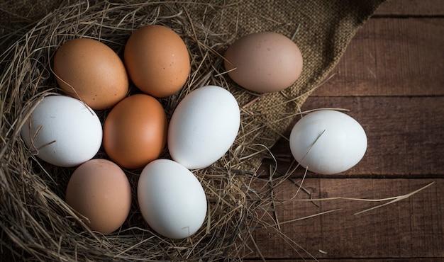 Uova marroni e bianche in un nido sonnolento su un fondo di legno marrone con tela da imballaggio.