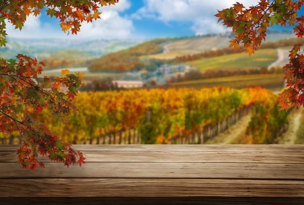 Tavolo in legno marrone nel paesaggio autunnale del vigneto con spazio vuoto per il mockup di visualizzazione del prodotto.
