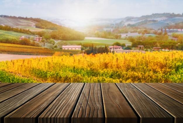 Tavolo in legno marrone nel paesaggio autunnale del vigneto con spazio vuoto per l'esposizione del prodotto